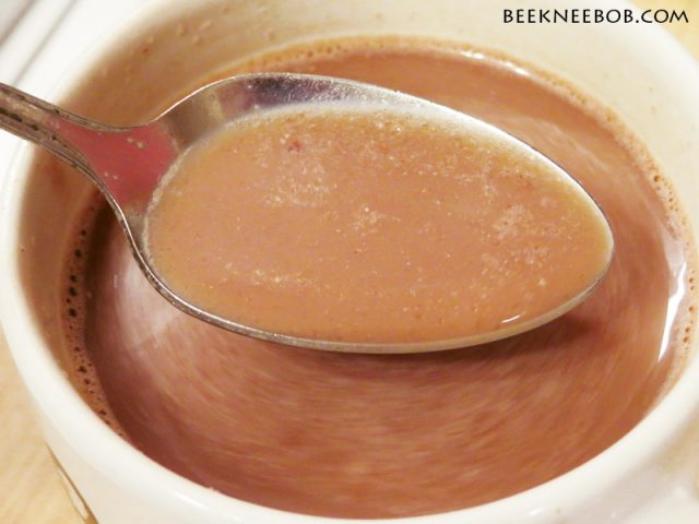 A spoonful of hot chocolate over the full mug